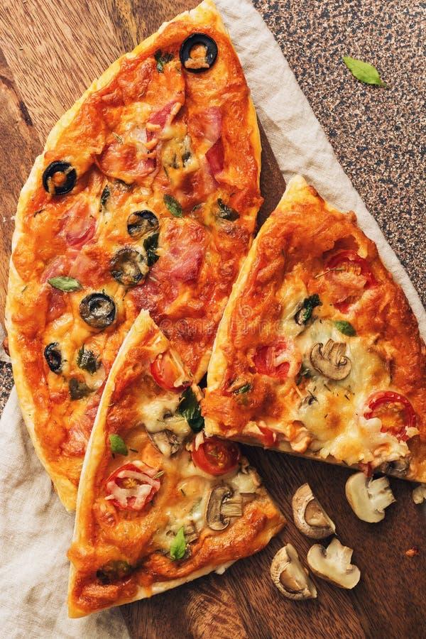 Pizza hecha en casa con las setas, el tomate y el queso Pizza con el jamón, las aceitunas y el queso en una tabla de cortar Dos p imagen de archivo libre de regalías