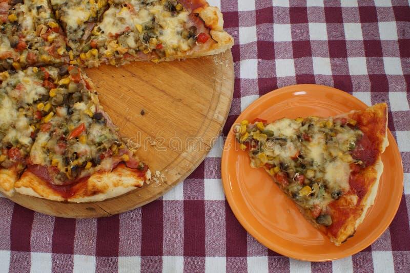 Pizza hecha en casa con un pedazo cortado que miente al lado de él fotografía de archivo
