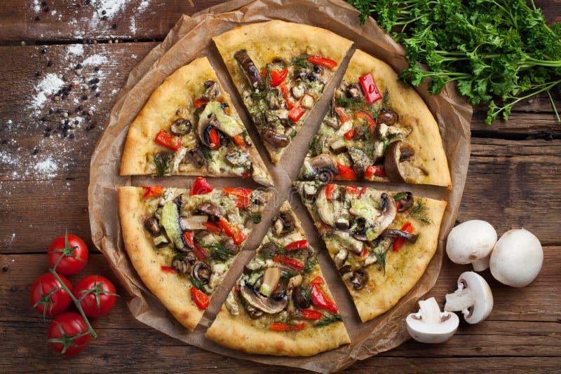 Pizza hecha en casa del vegano con los tomates, los paprikas, las setas y el hinojo en una tabla de madera vieja Visión superior foto de archivo libre de regalías