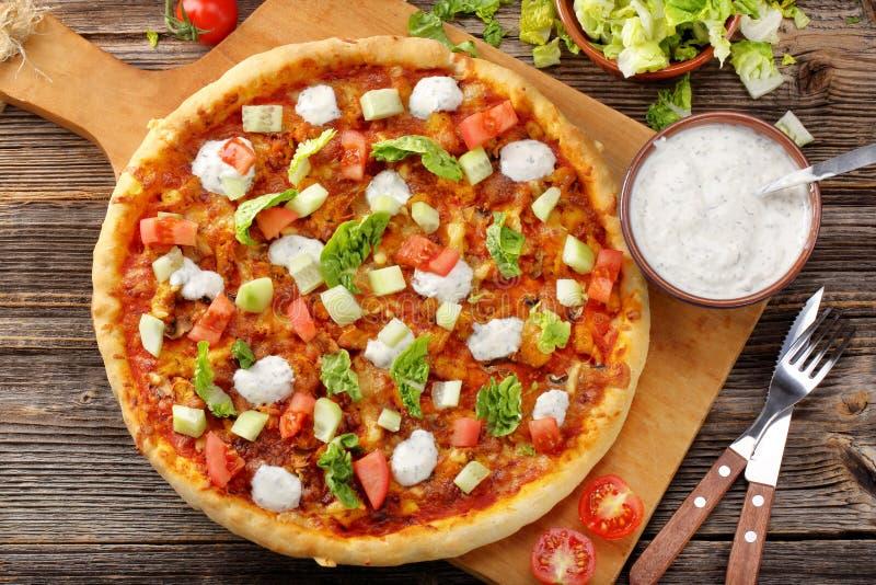 Pizza hecha en casa fresca con la salsa del pollo y de ajo en el CCB de madera foto de archivo libre de regalías