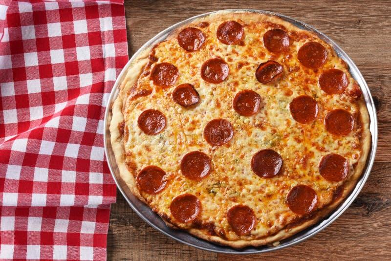 Pizza hecha en casa fresca de Pepproni en un mantel a cuadros rojo imagenes de archivo