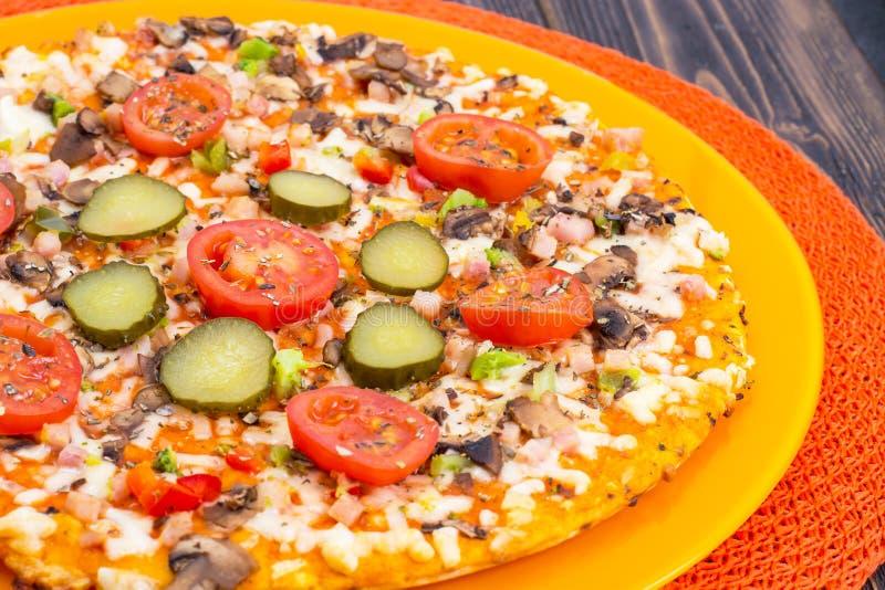 Pizza hommemade on orange plate. Studio Photo royalty free stock images