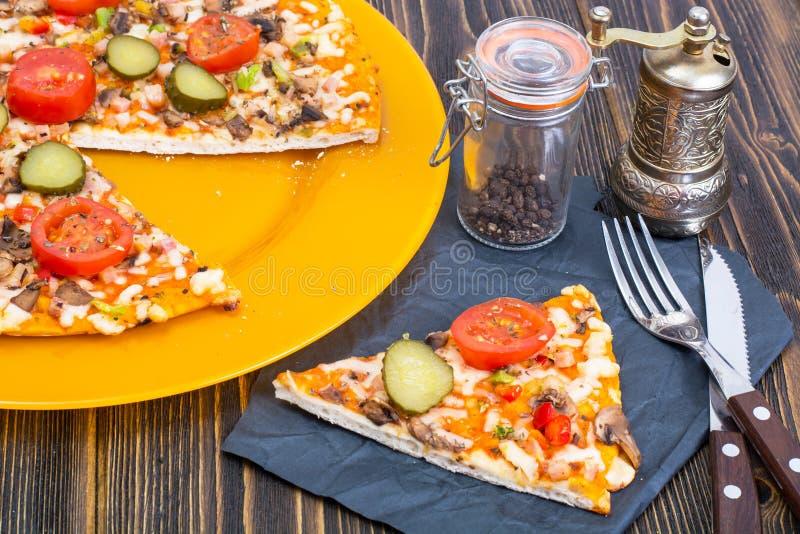 Pizza hommemade on orange plate. Studio Photo stock image