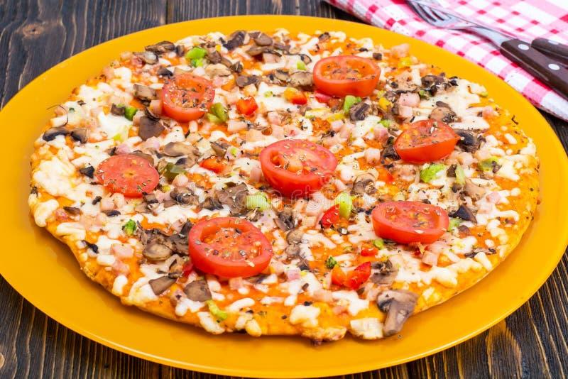 Pizza hommemade on orange plate. Studio Photo royalty free stock photos