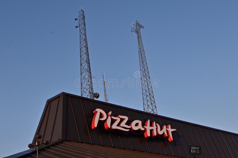Pizza Hut-signage met radio erachter torens stock fotografie