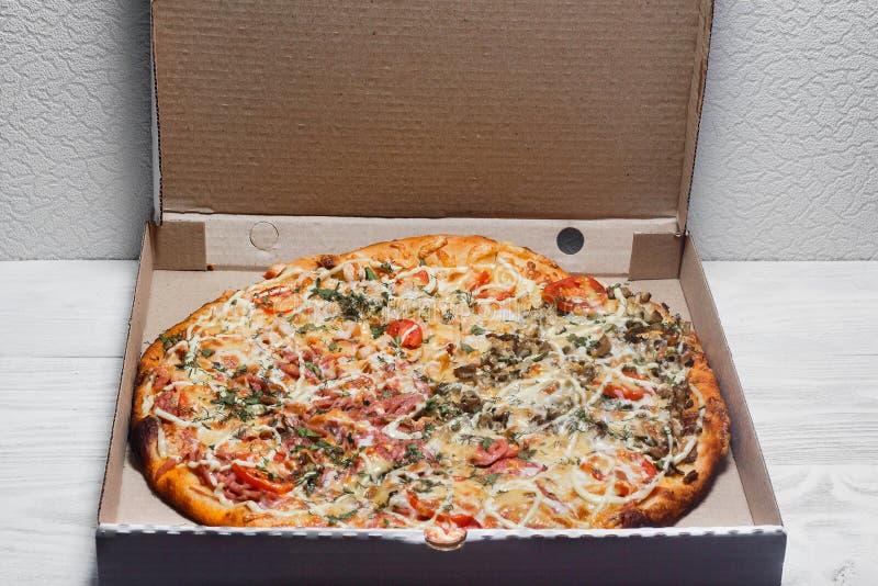 Pizza i en kartong på en vit träbakgrund ovanför sikt Gladlynt ungt bud som rymmer en pizzaask, medan isolerat på vit Pizzameny royaltyfri foto