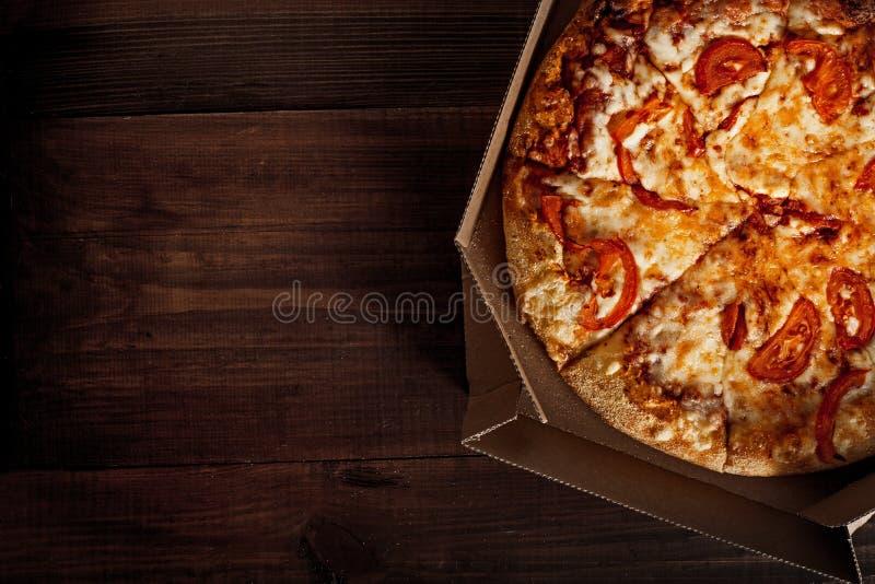 Pizza i i leveransask på trät arkivfoton