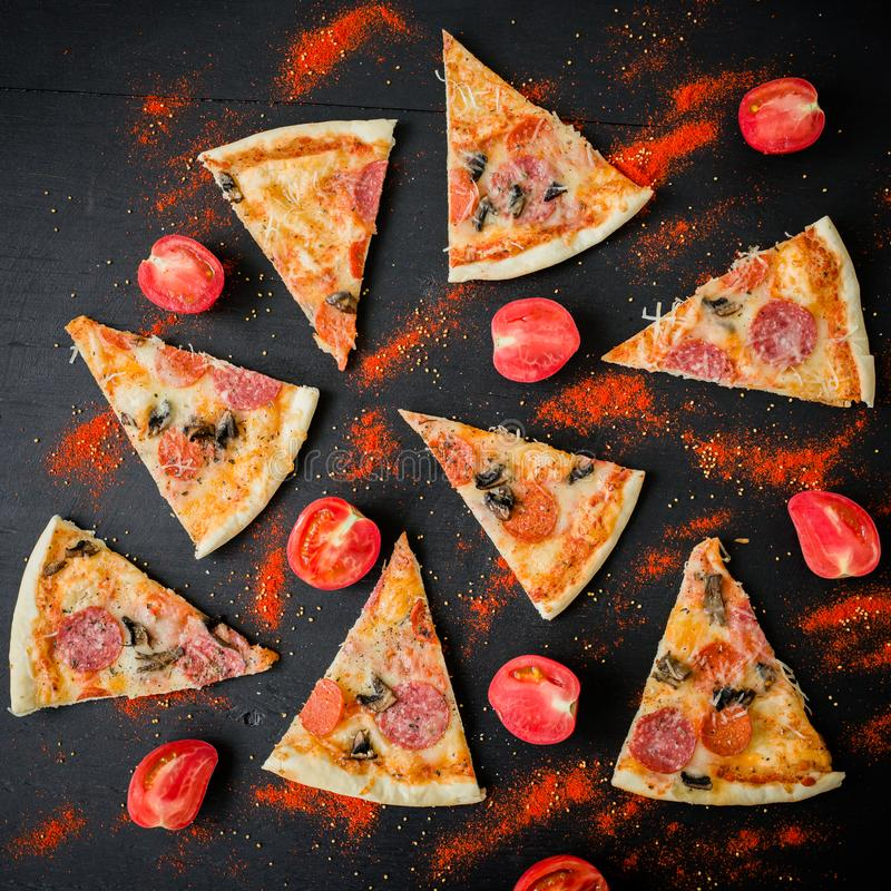 Pizza with ingredients on dark table. Pattern of pizza slices and tomato. Flat lay, top view. royalty free stock photo