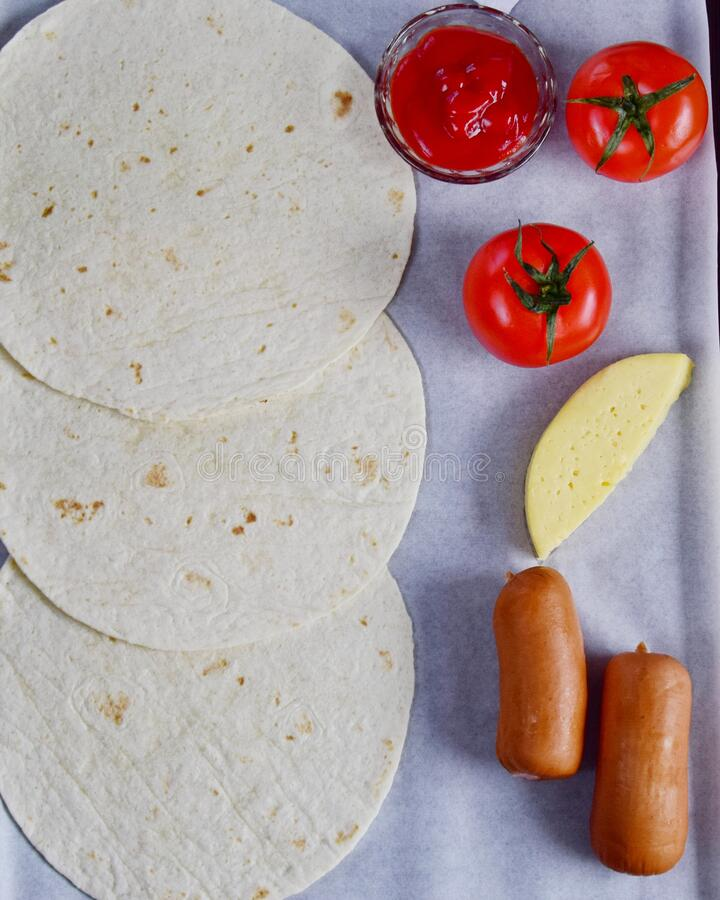 pizza ingredients are on the table, tomatoes, ketchup, sausages and pita bread top view, shot at a 90-degree angle stock photo