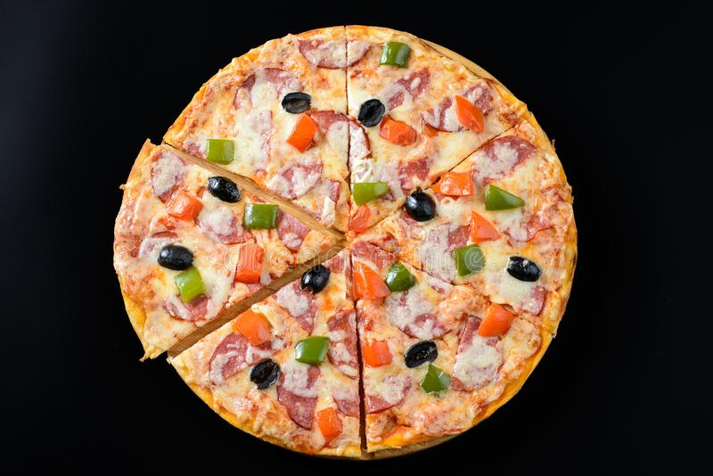Pizza isolated on black. Whole hot Pizza isolated on black background royalty free stock photography