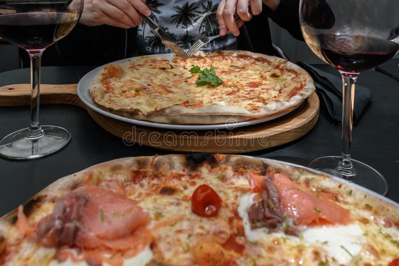 Cut pizza with shrimp and cheese and two wine glasses, smoked salmon pizza in foreground blurred royalty free stock photos