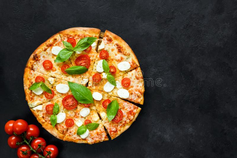 Pizza italiana caliente con los tomates, la albahaca y la mozzarella en fondo de piedra negro imagen de archivo libre de regalías