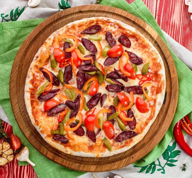 Pizza italiana com caça de salsichas, de tomates, de pimentas de pimentão, de queijo e de salmouras em uma placa de madeira redon fotos de stock