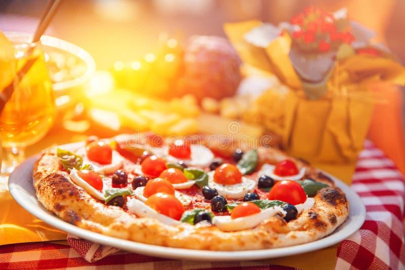 Pizza italiana com tomates, mozzarella, manjericão, azeitonas pretas No fundo, no vinho e no destaque da luz em foto de stock royalty free