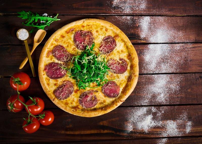 Pizza italiana con carne de vaca en una tabla de madera imagen de archivo