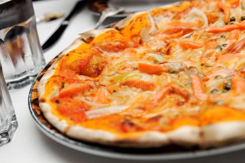 Pizza italiana con el desmoche de color salmón imagenes de archivo