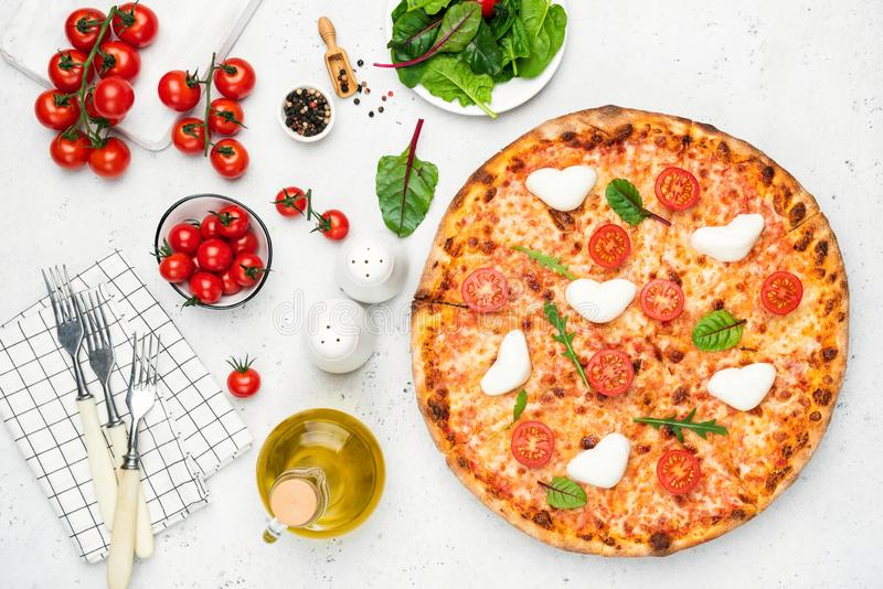 Pizza italiana con la mozzarella, los tomates y la albahaca en forma de corazón fotos de archivo