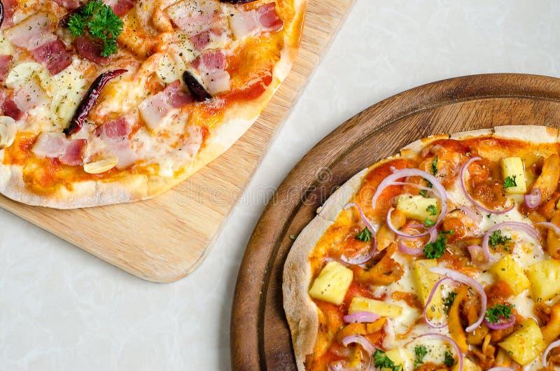 Pizza italiana del BBQ del pollo hawaiano e pizza italiana del bacon, dell'aglio e dei peperoncini rossi sul piatto di legno immagine stock libera da diritti