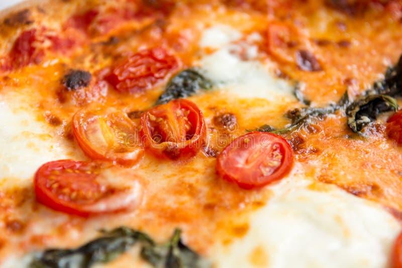 Pizza italiana deliciosa del estilo con los tomates, mozarella y albahaca imagen de archivo