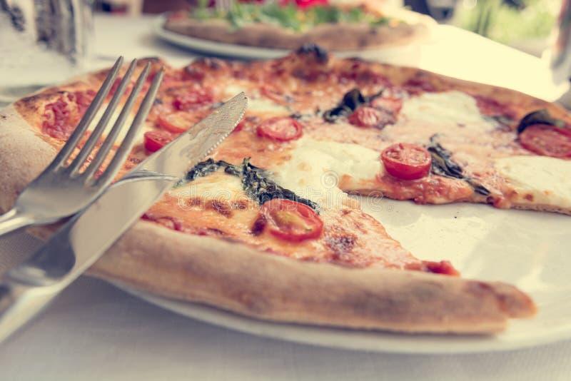 Pizza italiana deliciosa del estilo con los tomates, mozarella y albahaca fotografía de archivo libre de regalías