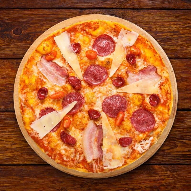 Pizza italiana deliziosa con salame, bacon e parmigiano fotografia stock libera da diritti