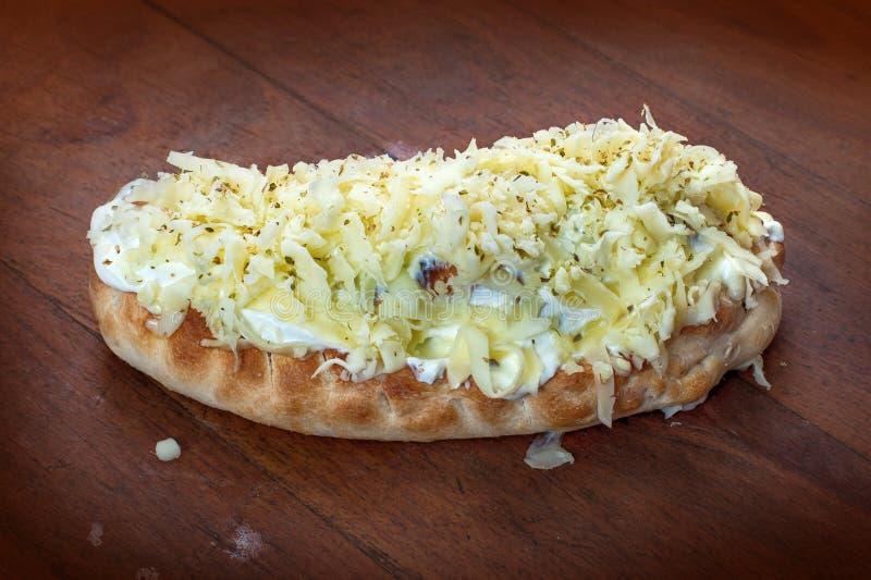 Pizza italiana della piroga sulla tavola di legno con la fusione del formaggio al forno immagini stock