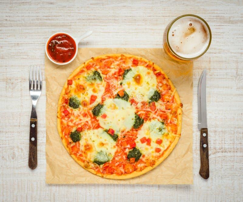 Pizza italiana di cucina con birra e salsa al pomodoro fotografia stock