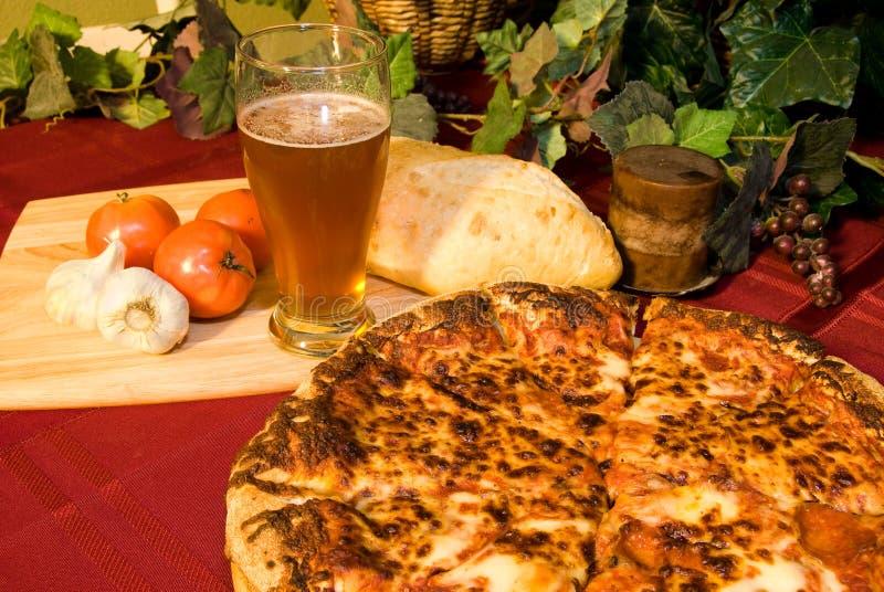 Pizza italiana e cerveja fria imagem de stock