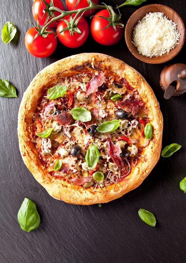 Pizza italiana fresca servita sulla pietra nera fotografie stock
