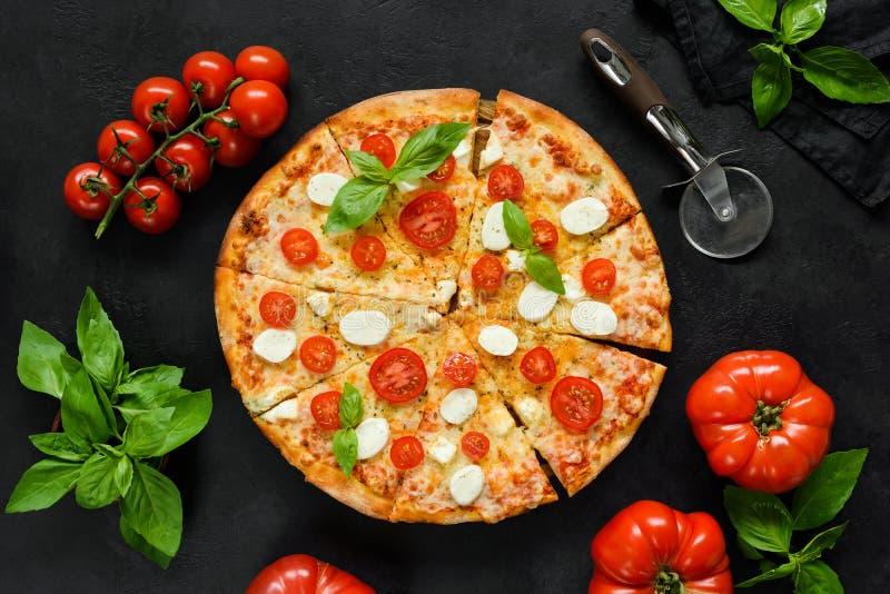 Pizza italiana hecha en casa con la mozzarella, los tomates y la albahaca en el contexto concreto negro imágenes de archivo libres de regalías