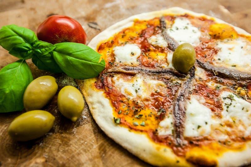 Pizza italiana originale Napoletana su fondo di legno marrone La pizza con le acciughe ed i capperi si chiudono su fotografia stock