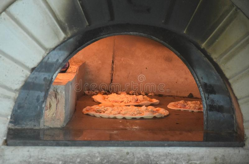 Pizza italiana que cocina en un horno de la tradición foto de archivo libre de regalías