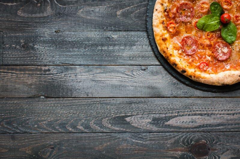 Pizza italiana quente em uma tabela de madeira rústica imagem de stock