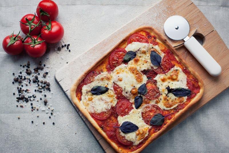 Pizza italiana rústica con las hojas de la mozzarella, del queso y de la albahaca fotografía de archivo