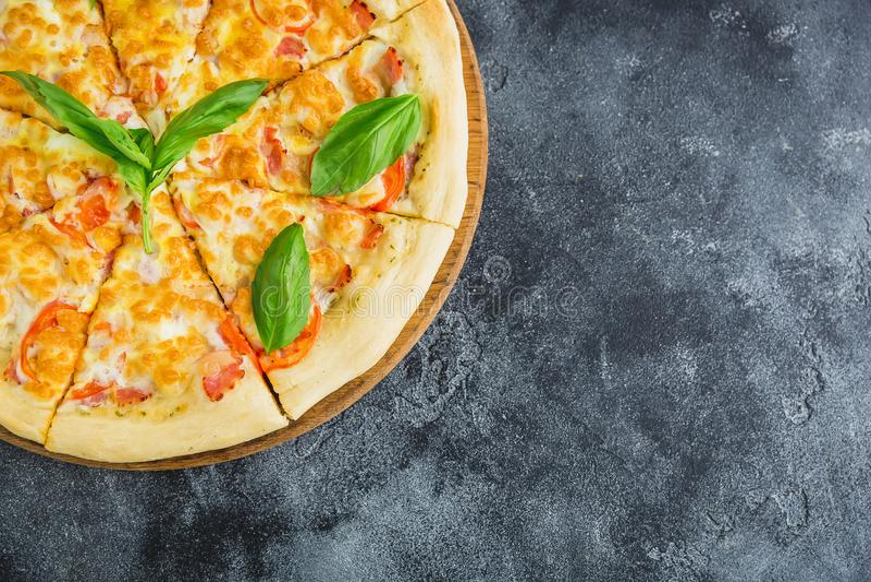 Pizza italiana sabrosa con el tocino, queso, tomate en fondo oscuro Endecha plana, visión superior imagen de archivo