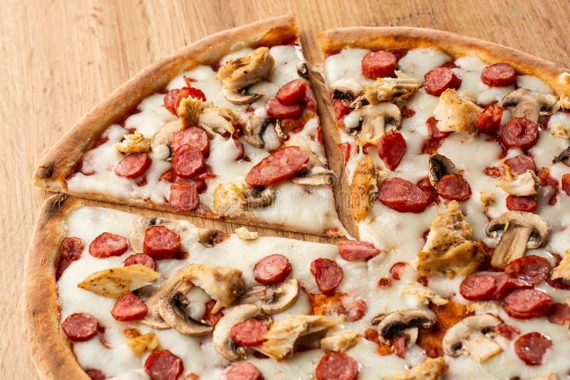 Pizza italiana saporita su fondo di legno Vista superiore di pizza con le salsiccie, il pollo, i funghi, i pomodori ed il formagg fotografia stock