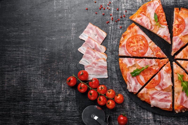 Pizza italiana tradicional com mozzarella, presunto, tomates, pimenta, especiarias dos pepperoni e o rucola fresco foto de stock