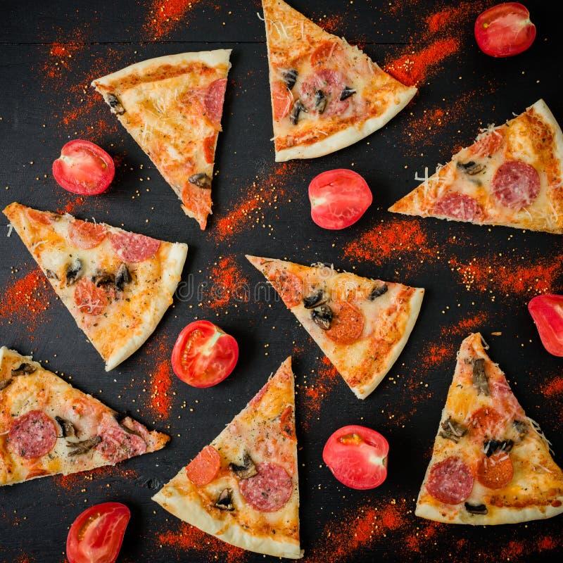 Pizza italienne avec des ingrédients Configuration plate, vue supérieure La pizza ébrèche le modèle sur la table foncée photographie stock