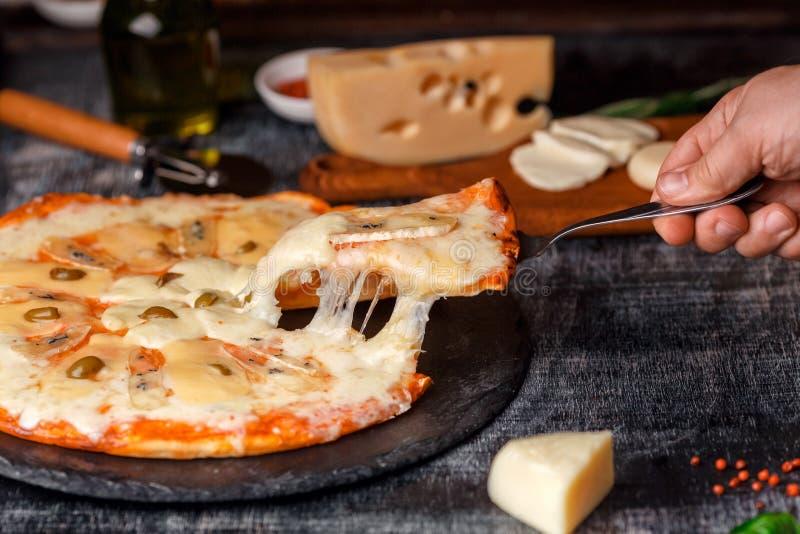 Pizza italienne avec différentes sortes de fromage sur une pierre et un panneau de craie rayé noir Nourriture traditionnelle ital photographie stock libre de droits