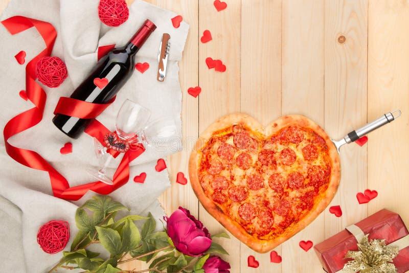 Pizza italienne en forme de coeur avec les pepperoni et la bouteille de mozzarella et de vin rouge images stock