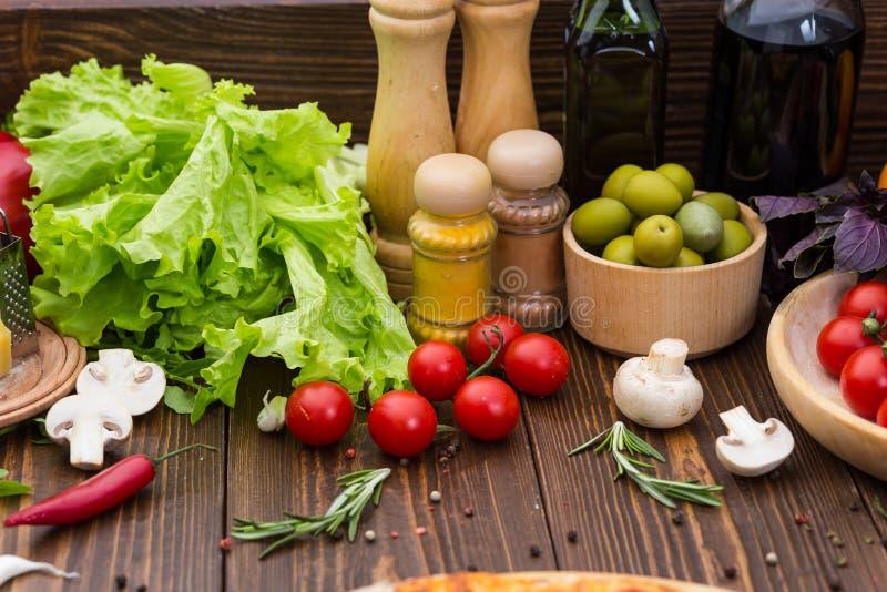 Pizza kokende ingrediënten Deeg, groenten, kaas en kruiden stock foto's