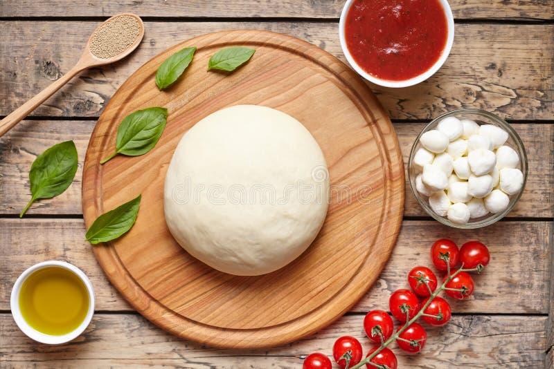Pizza kokende ingrediënten op scherpe raad Deeg, mozarella, tomaten, basilicum, olijfolie, kruiden Het werk met het deeg stock afbeeldingen