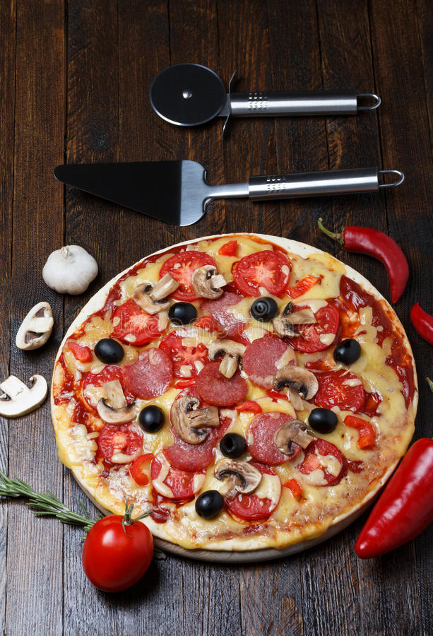 Pizza with lifter and cutter. On wooden table stock image