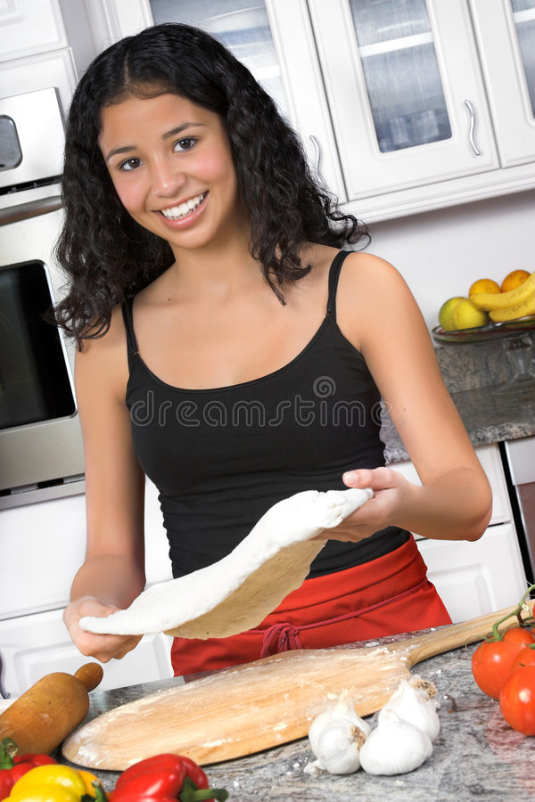 Pizza making. Young woman making pizza in kitchen royalty free stock photography