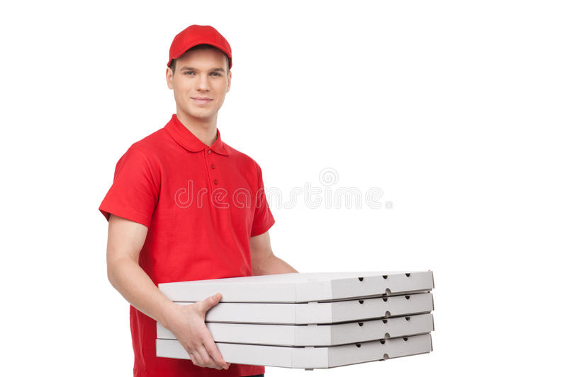 Pizza man. Cheerful young deliveryman holding a pizza box while. Isolated on white royalty free stock photos