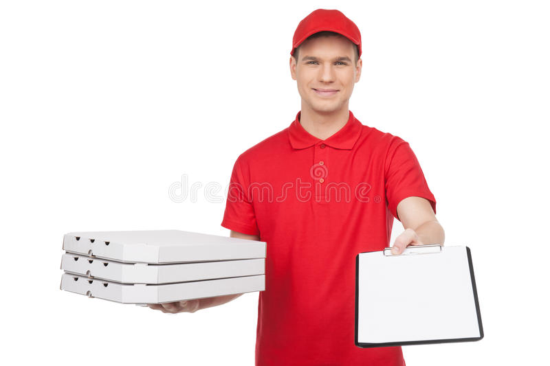 Pizza man at work. Young cheerful pizza man holding a stack of p. Izza boxes and stretching out a clipboard while isolated on white royalty free stock photography