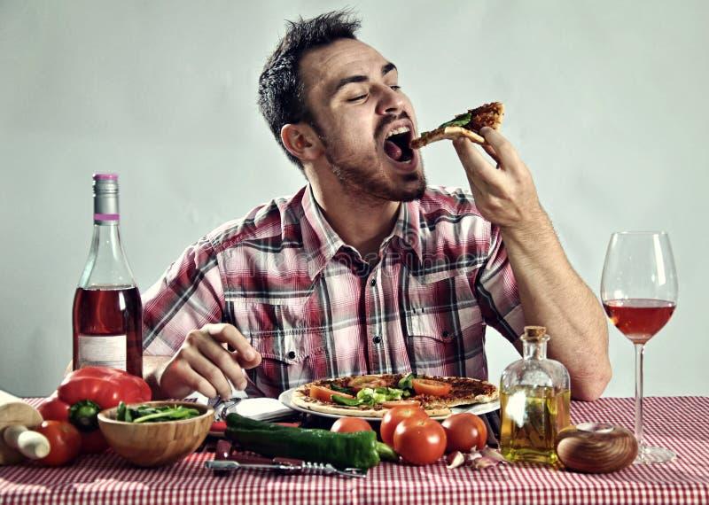 Pizza mangeuse d'hommes affamée folle photographie stock