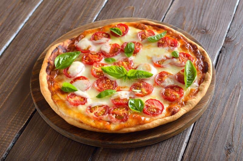 Pizza Margarita en tabla de cortar de madera fotografía de archivo libre de regalías