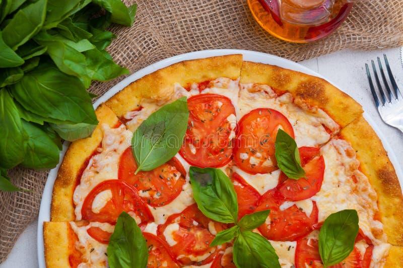 Pizza Margarita met kaas en hete saus op een lichte lijst Hoogste mening stock afbeeldingen