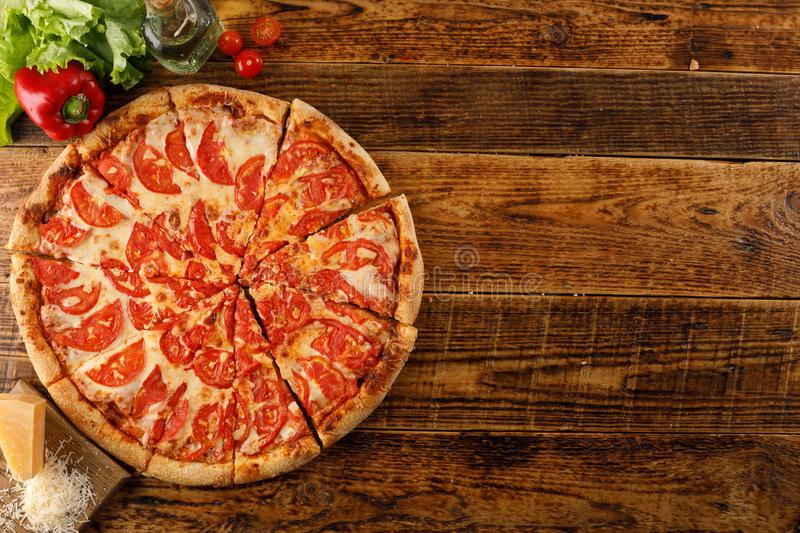 Pizza Margarita on a wooden table. Still life with ingredients royalty free stock photos